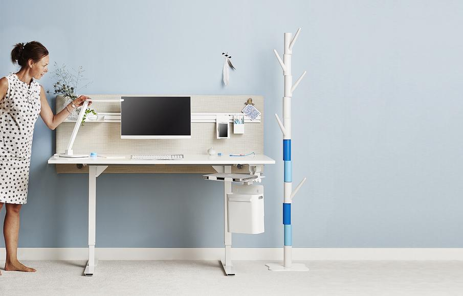 Vrouw kijk naar een zit/sta bureau met ergonomisch ingerichte werkplek